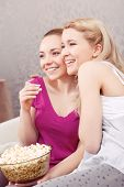stock photo of pajamas  - Comedy movie. Two young beautiful girls sitting on a white couch watching a movie and hugging each other while eating popcorn at pajama party side view