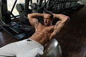 stock photo of abdominal  - Muscular Mature Man Exercising Abdominals On Exercise Ball In Modern Fitness Center - JPG