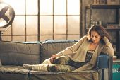 picture of legs apart  - An elegant brunette woman wearing comfortable casual clothing leggings and a cardigan is relaxing on a sofa in a loft. Sunlight shines through the window. 