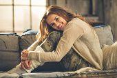 stock photo of comfort  - An elegant brunette woman is smiling hugging her knees - JPG
