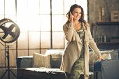 stock photo of comfort  - Seen from the front a brunette woman in comfortable clothing is standing in a loft living room leaning against the sofa talking on her phone and smiling - JPG