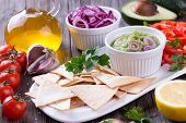 pic of nachos  - Guacamole in porcelain Bowl with mexican Tortilla Chips nachos and Ingredients - JPG
