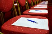 Постер, плакат: Chairs With Notepads And Pens In Empty Conference Room