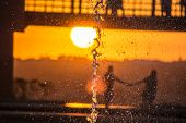stock photo of fountains  - Couple holding hands on sunset behind a water fountain - JPG