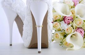 picture of stiletto  - Wedding Day concept with rings on heel of beautiful white floral bridal stiletto shoes with bouquet on white shabby chic wood table - JPG