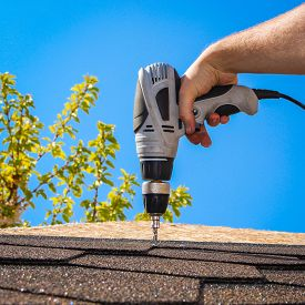 pic of shingles  - The man puts a soft roof on a house roof - JPG