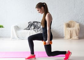 stock photo of stand up  - Athletic woman warming up doing weighted lunges with dumbbells workout exercise for butt legs at home healthy lifestyle sport bodybuilding concept - JPG