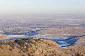 pic of horsetooth reservoir  - typical hazy winter afternoon over Fort Collins Colorado with frozen Horsetooth Reservoir some snow clear sky but with a brown layer of dust and aerosols in the air - JPG