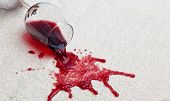 stock photo of embarrassing  - A toppled glass of red wine with a dirty carpet - JPG