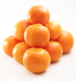 stock photo of tetrahedron  - A pile of orange citrus fruits arranged in a tetrahedron pyramid shape - JPG