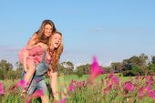 stock photo of bff  - happy smiling spring or summer piggy back teens or teenager kids - JPG