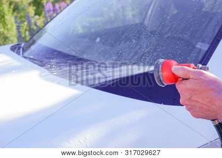 poster of Car Warhing. Worker Cleaning White Car On Open Air.cleaning Car Using High Pressure Water. Man Washi