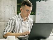 Young Concentrated Male White Collar In Loft Office Working By Laptop poster