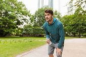 Photo of unshaven man wearing sportswear listening music with earphones and holding bottle of water  poster