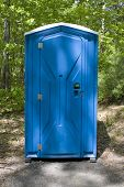 pic of porta-potties  - A blue porta potty located on the wooded hiking trail - JPG