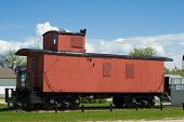 pic of caboose  - A red train caboose sitting on some railroad tracks outside - JPG
