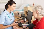 British nurse taking senior woman's blood pressure
