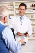 stock photo of dispenser  - American pharmacist with senior man in pharmacy - JPG