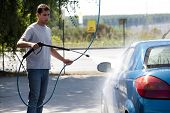image of car wash  - Young man washing his car with compression water - JPG