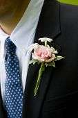 A detail photo of a grooms wedding boutonniere. Green and pink flowers