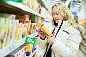 woman choosing bio produces during food shopping in grocery store supermarket