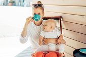 Caucasian Young Woman Sits In A Deck Chair At The Table, Drinks Coffee And Holds The Baby In Her Arm poster