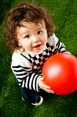 image of cute little girl  - little kid with a red ball on the green grass - JPG