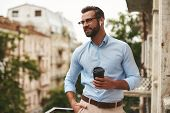 Nice Talk. Young And Handsome Bearded Man In Eyeglasses And Headphones Holding Cup Of Coffee And Tal poster