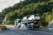 Car Transporter Carrying. Injured Cars Transported On The Car Platform On A Mountain Road. Truck Car poster