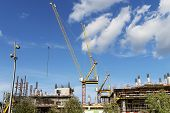 Two Construction Cranes On A Building Construction. High Crane On A Blue Sky With Clouds. The Constr poster