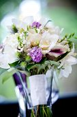 A brides wedding bouquet of flowers sitting in a vase full of water. Very shallow depth of field, fo