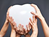 image of threesome  - Multiple hands are holding a heart balloon - JPG