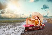 picture of children beach  - Funny baby girl traveler sitting in retro suitcase at the sea coast - JPG