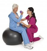 foto of personal assistant  - Female health care professional assisting female senior citizen with exercise technique - JPG