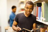 picture of librarian  - male african college student reading in library - JPG