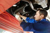stock photo of gasoline station  - car mechanic tighten screw in make suspension adjustment with spanner during automobile wheel alignment work at repair service station - JPG