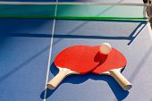 picture of ping pong  - table tennis ping pong two paddles and white ball on blue board - JPG