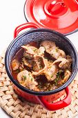 picture of giblets  - Stewed chicken gizzards in red pan on the mat - JPG