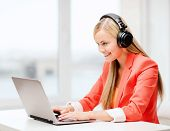 leisure, music, free time, online and internet concept - happy woman with headphones listening to mu