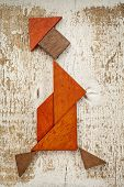 abstract figure of a walking woman built from seven tangram wooden pieces, a traditional Chinese puz