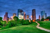 stock photo of texas  - Houston Texas modern skyline at sunset twilight from park lawn - JPG