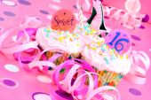 picture of sweet sixteen  - Two pink cupcakes with Sweet 16 on them in feminine setting - JPG