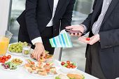 stock photo of buffet  - Office colleagues at office buffet with snacks