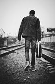 image of outlaw  - A young man with guitar case in hand is going away. Rear view black and white