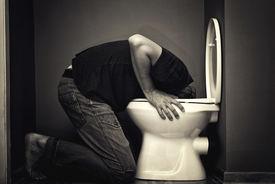 stock photo of vomiting  - Man vomiting in toilet bowl - JPG