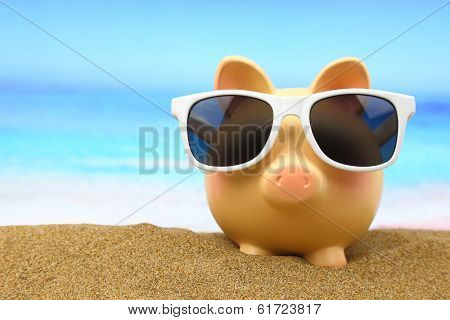 Summer piggy bank with sunglasses on the beach poster