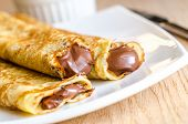 image of crepes  - Golden homemade crepes with dark chocolate cream - JPG
