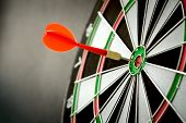 stock photo of throw up  - Right on target concept using dart in the bullseye on dartboard - JPG