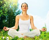 pic of  practices  - Young Woman doing Yoga Exercises Outdoor - JPG