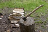 picture of ax  - Ax stuck in lumps next to chopped wood